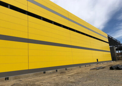 yellow IMP panels on the side of a building